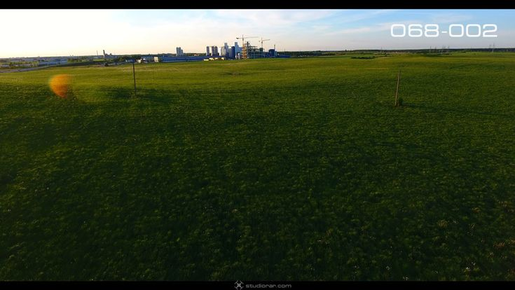 The meadows with a factory on the horizon – Drone Aerial Photography, Videogra...
