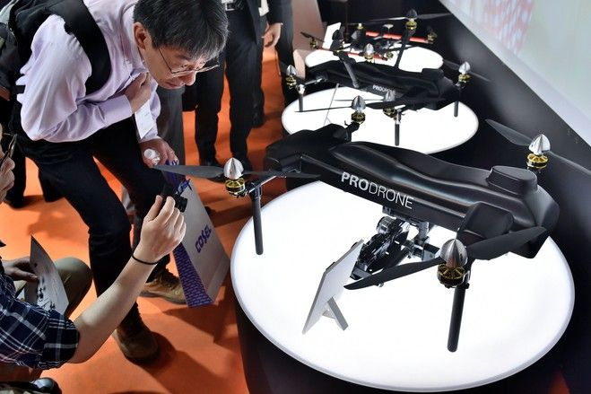 Exhibition visitors look at a drone developed by the Japanese industrial drone d...
