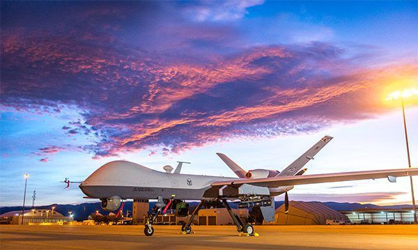 Military Drone: MQ-9 Reaper parked on a flightline below dramatic sunrise