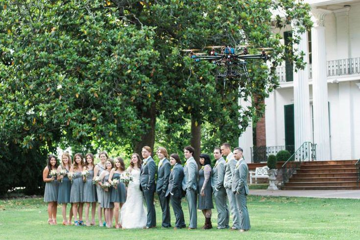 Wedding party smiling for the camera with a photography drone hovering above them #dronepicturesideas